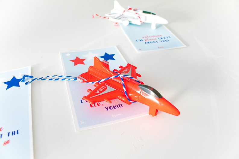 Red jet plane toy tied in bakers twine to attach to plane valentine printable card