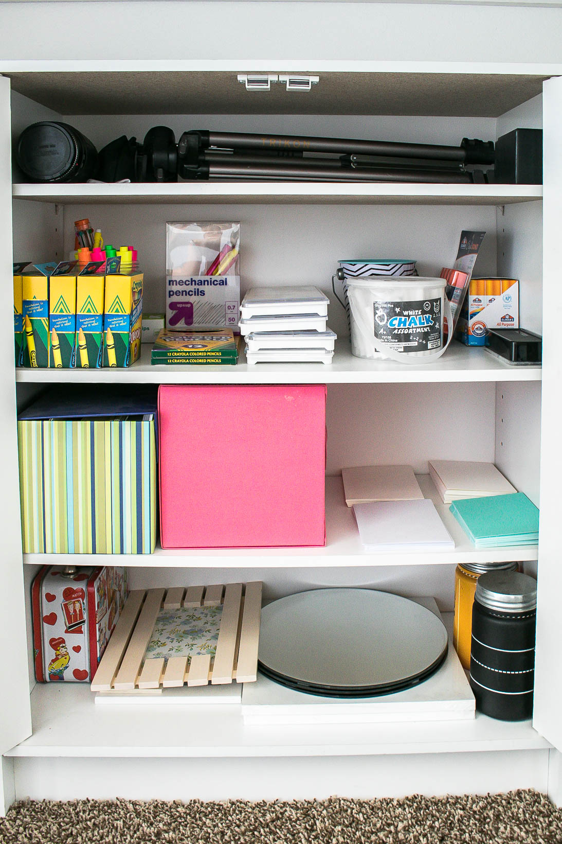 Craft supply storage in organized white craft room